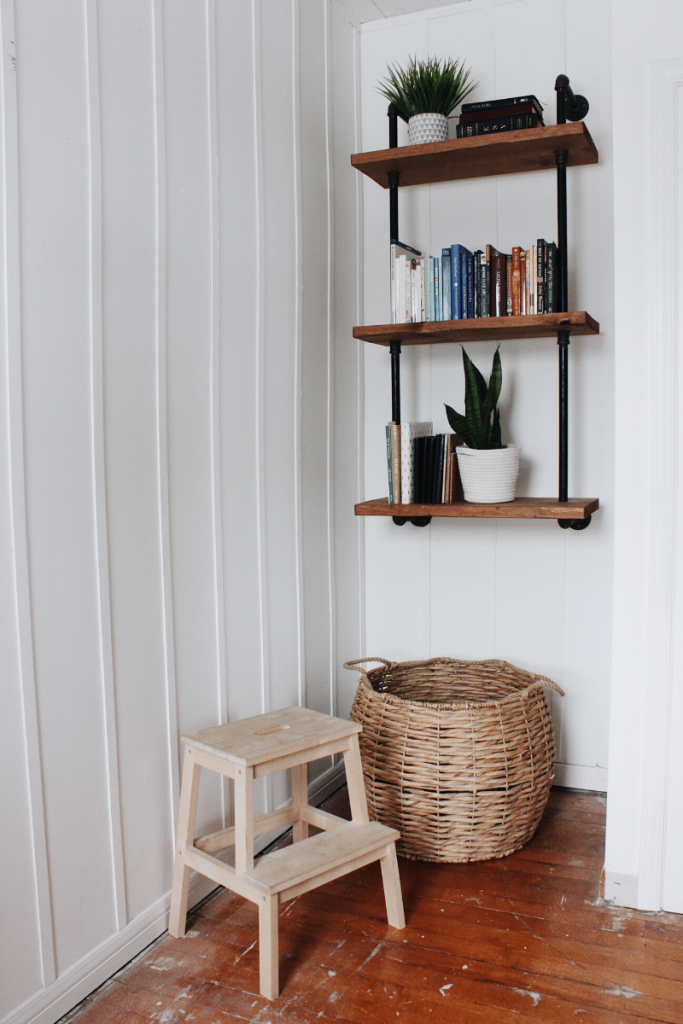 3 tiered iron and wood bookshelves sitting tucked inside a nook with laundry basket and stool below