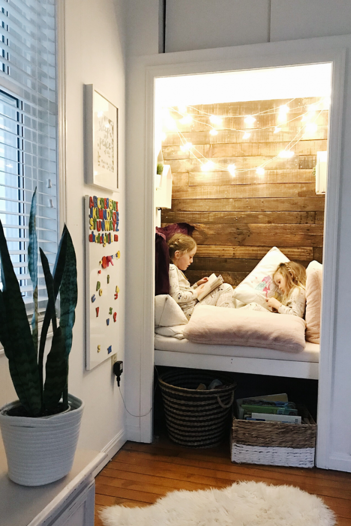 cozy nook reading nook inside bedroom closet with two little girls reading books
