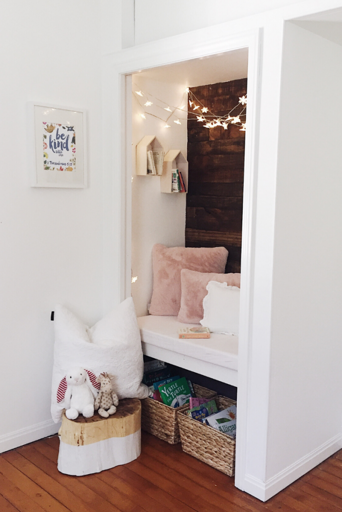 closet reading nook with twinkle lights hanging, pink pillows and stump stool with a pillow and stuffed animals sitting on top