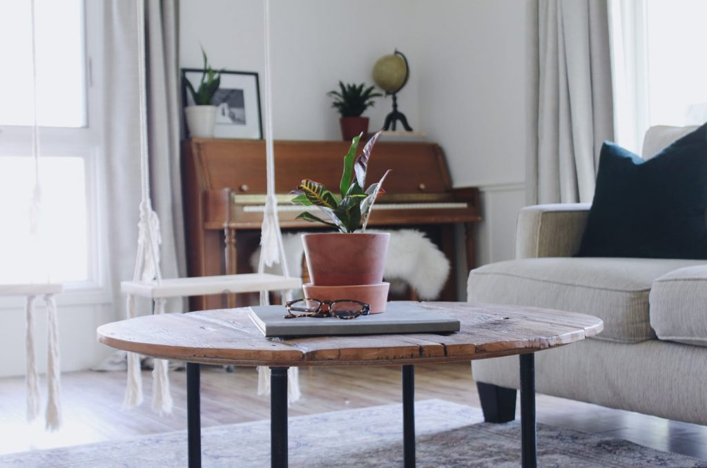 round wooden coffee table with plant and glasses on top, two indoor swings hanging behind