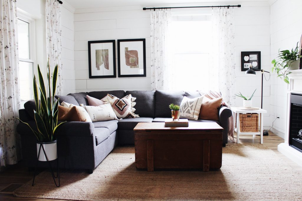 bright living room with shiplap walls are dark couch
