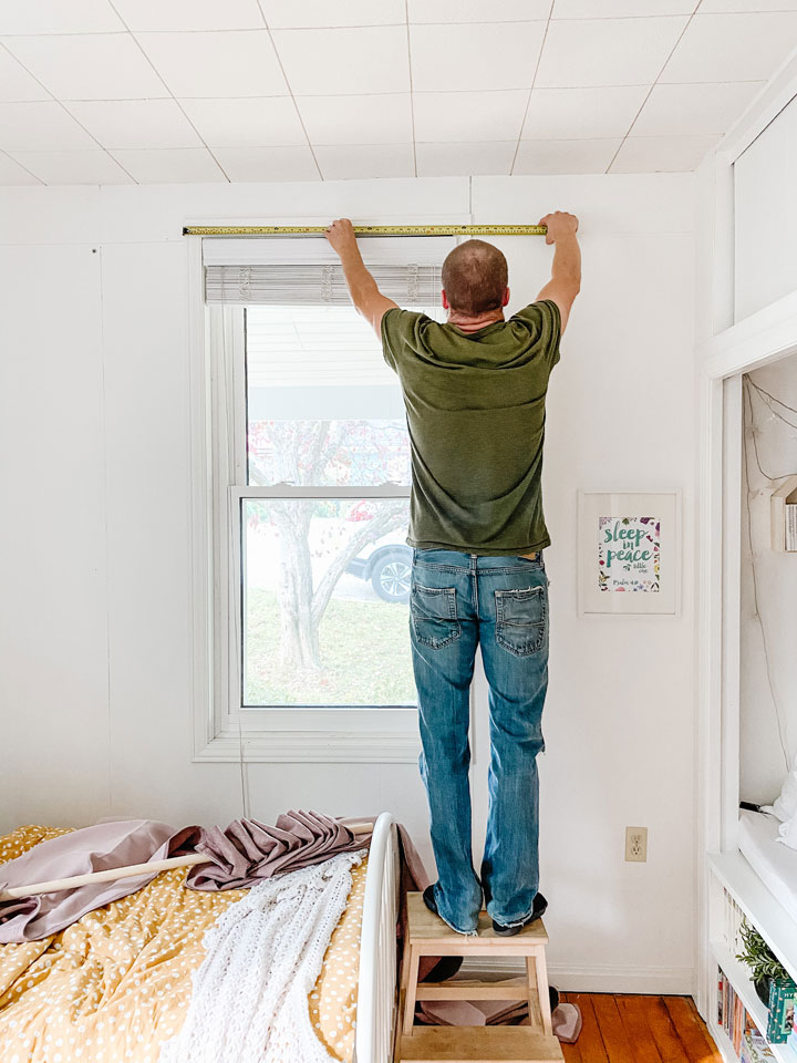 man measuring window casing