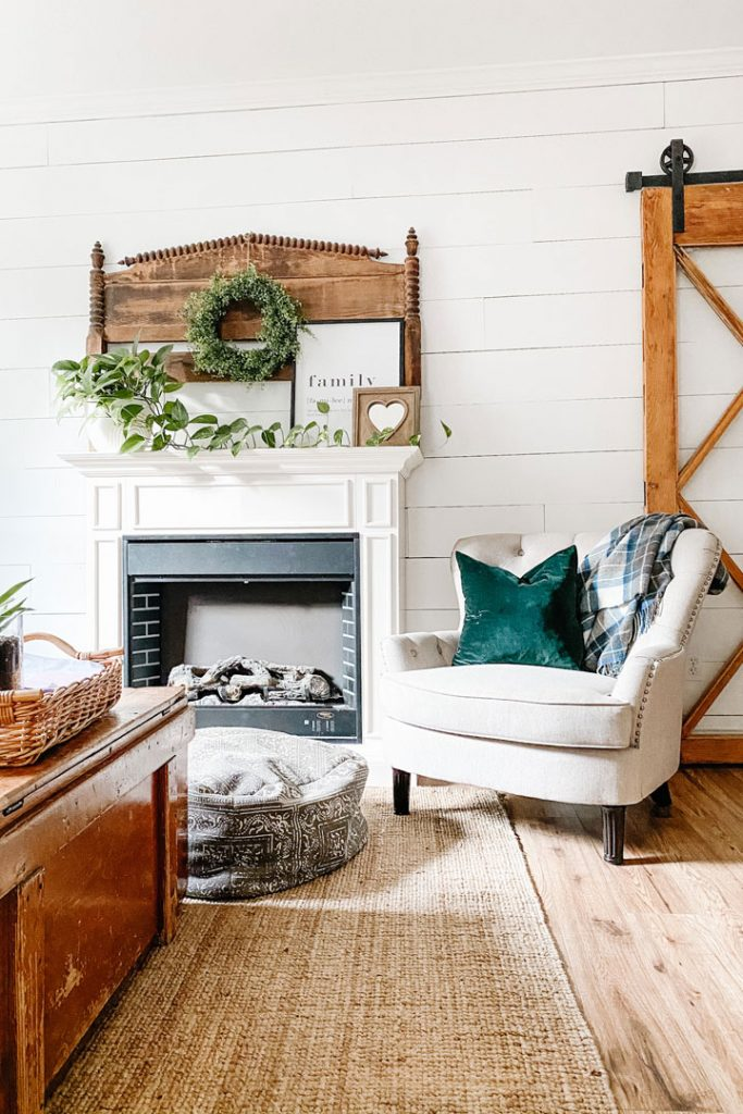 fireplace with oversized chair and shiplap walls
