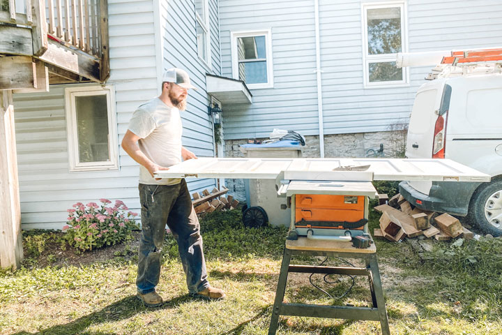 Man using table saw to trim down salvaged doors