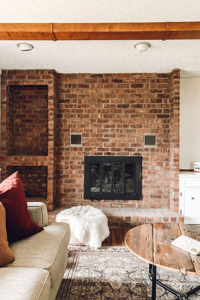 red brick firepalce with couch and coffee table in forground