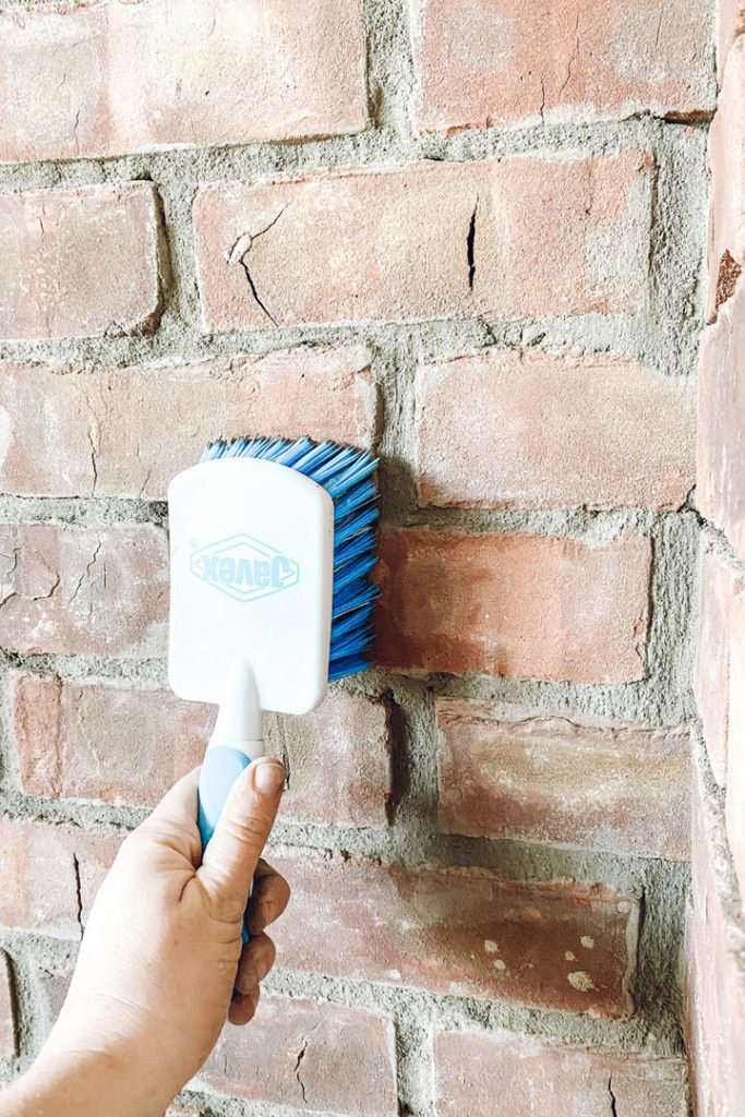 large scrub brush smoothing mortar a brick fireplace