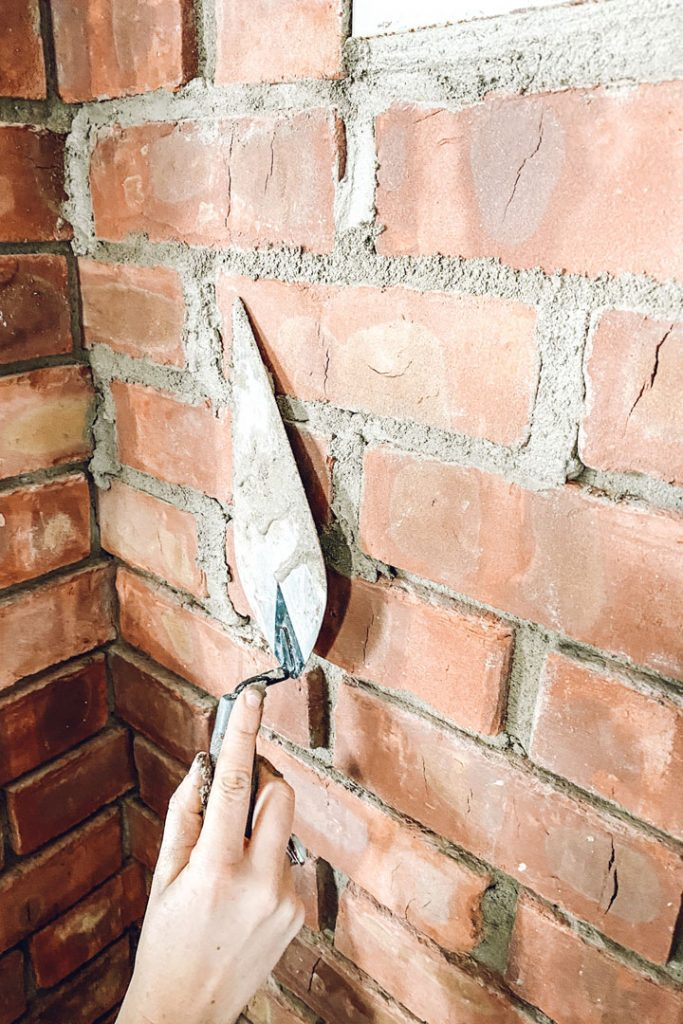 point trowel smoothing mortar a brick fireplace