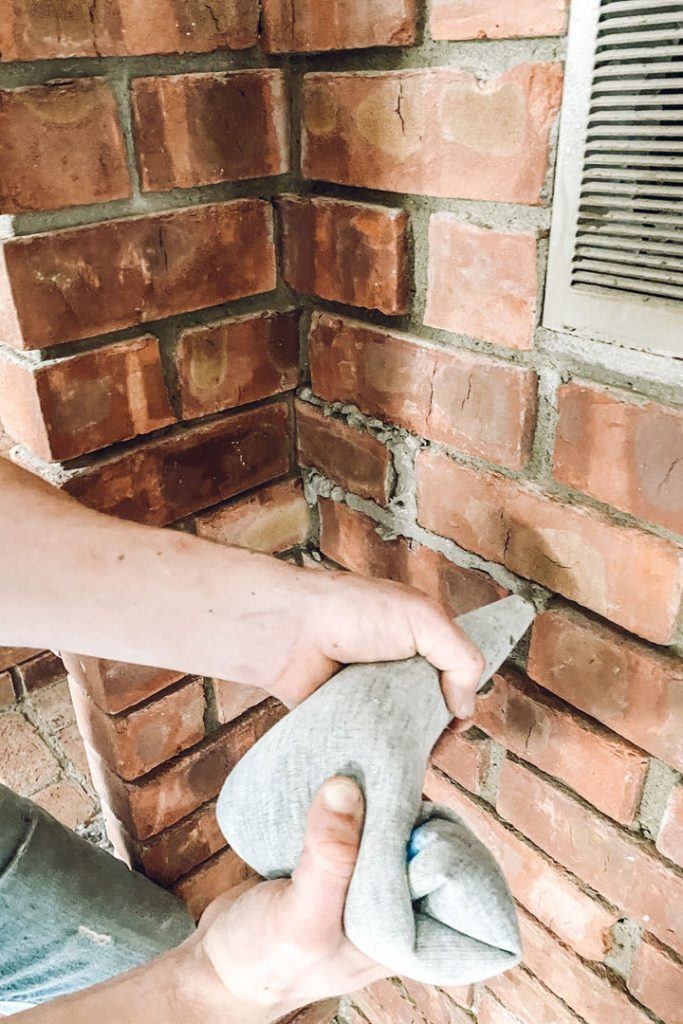 adding mortar to red brick fireplace
