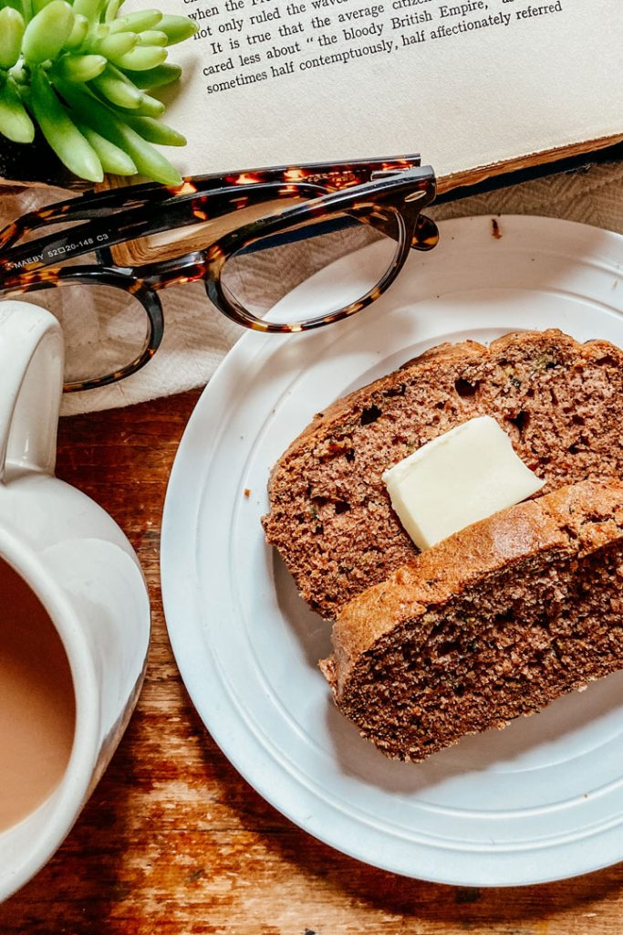 2 slices of gluten-free zucchini bread on top of a plate set down near glasses and a book