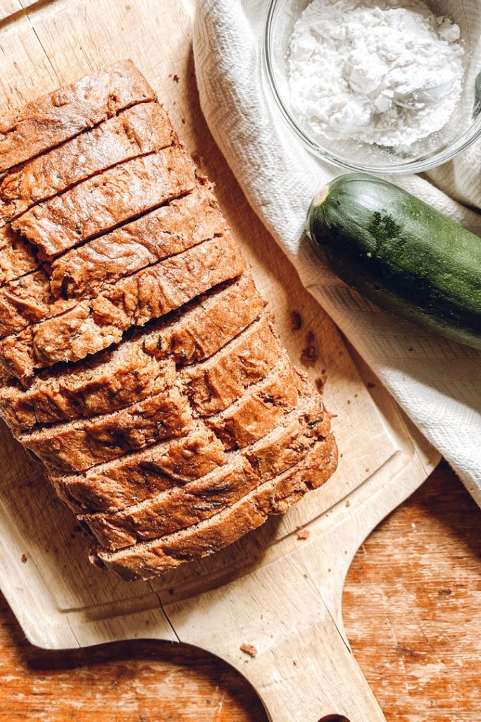 slided loaf of zucchini bread sitting on cutting board with zucchini and bowl of flour off to the right