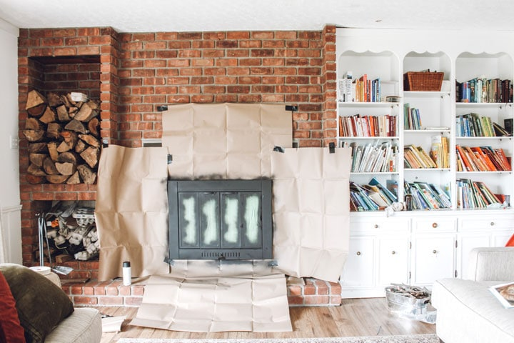 spray painted fireplace insert with kraft paper covering brick surround
