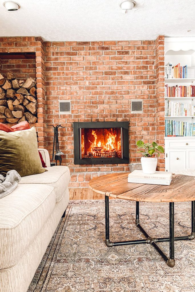 red brick fireplace with roaring fire, bookself to the right, wooden circular coffee table in forground