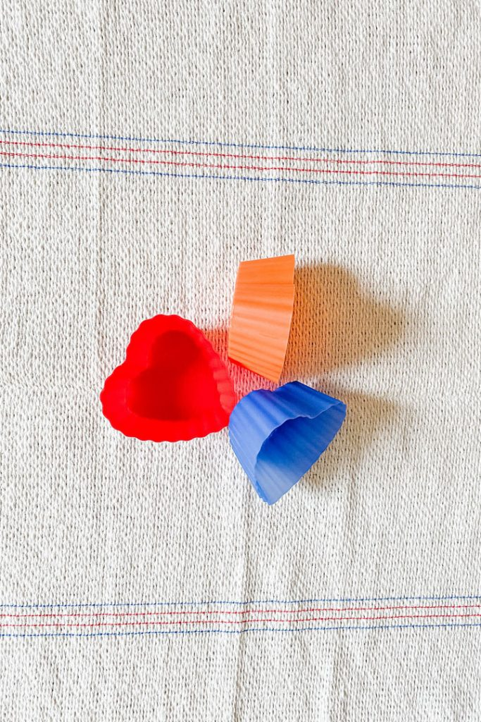 three heart shaped reuable muffin liners atop kitchen towel