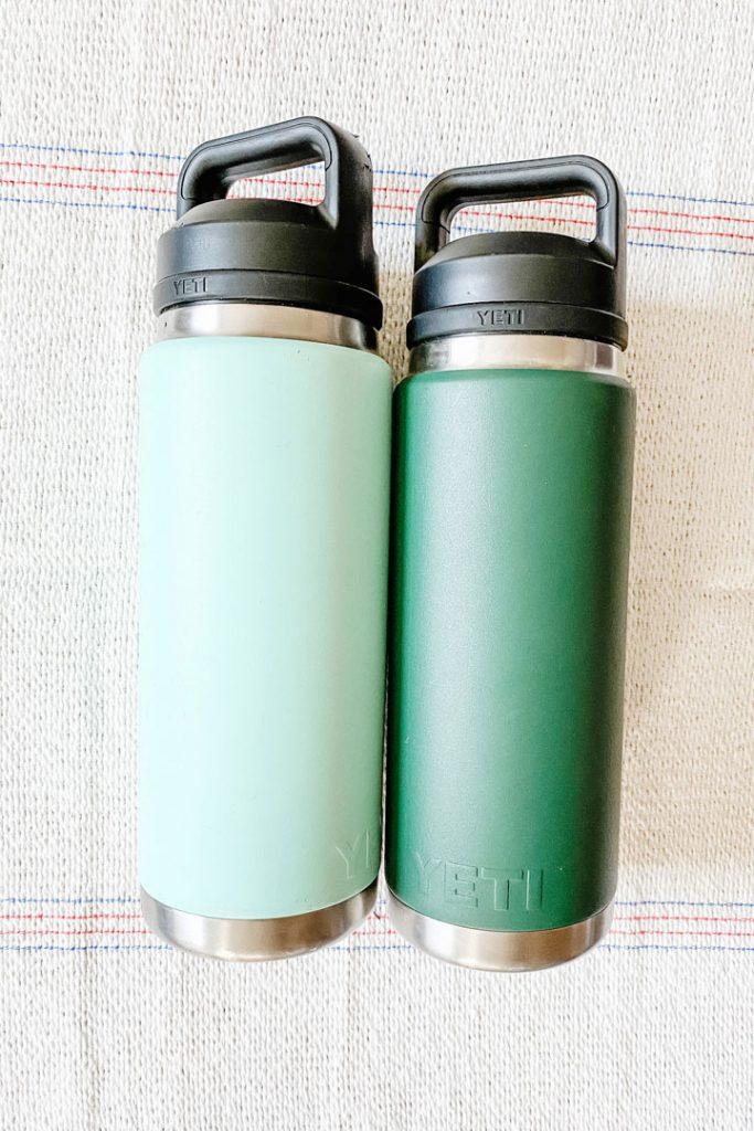 two yeti water bottles lying side by side