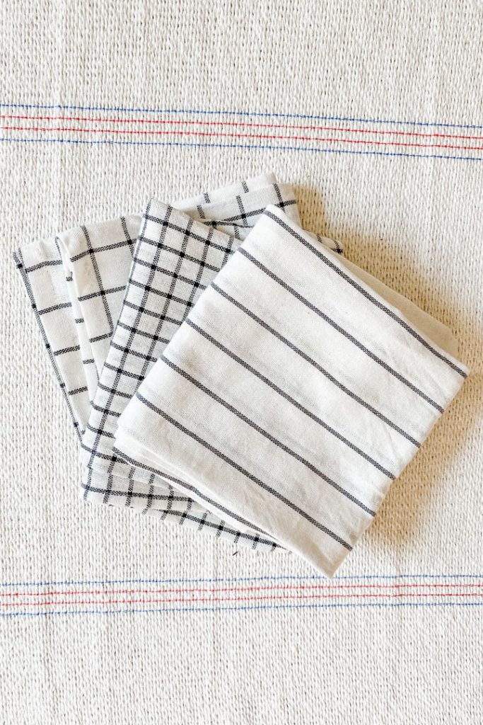 three eco-friendly kitchen napkins fanned out across background
