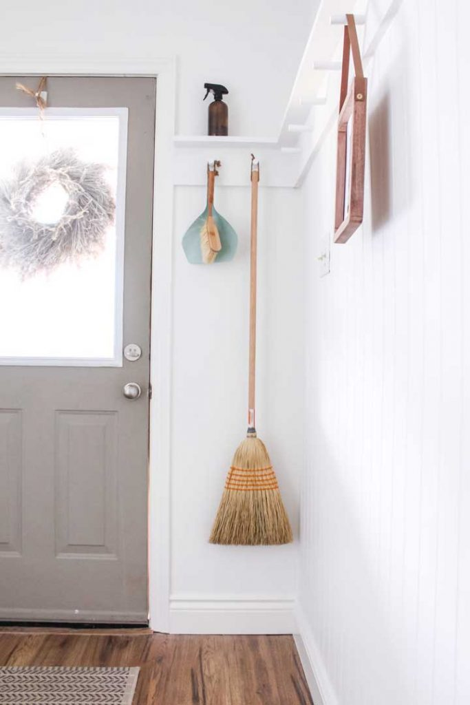 peg rail storage for broom and dust pan at front entrance