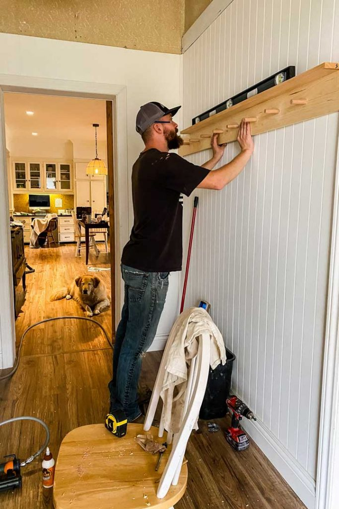 Level peg rail with shelf on wall and fasten to studs using wood screws