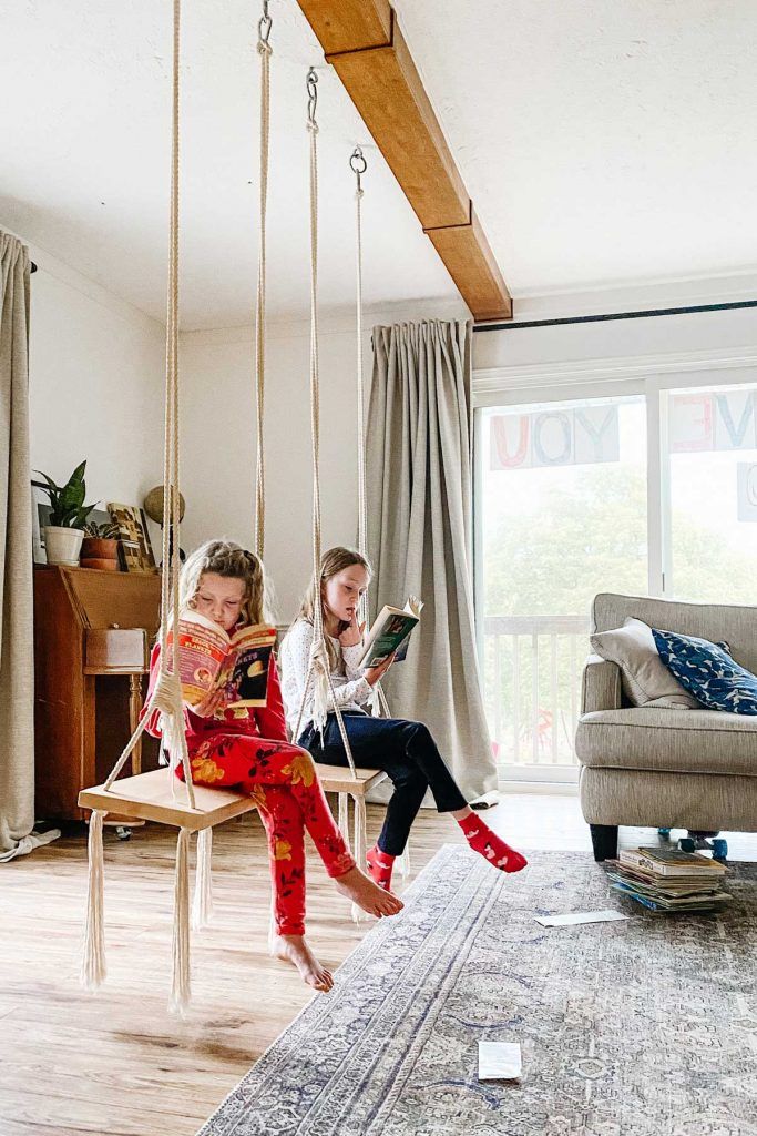 two diy indoor swings with two girls sitting on them reading books