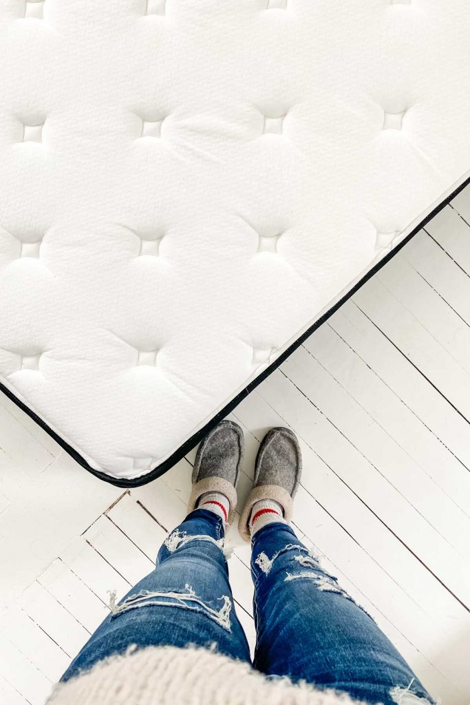 bird's eye view of Hamuq mattress and womens legs with ripped jeans and gray slippers