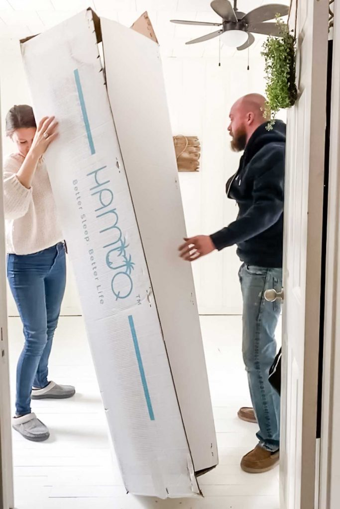 man and women moving Hamuq mattress in a box into bedroom
