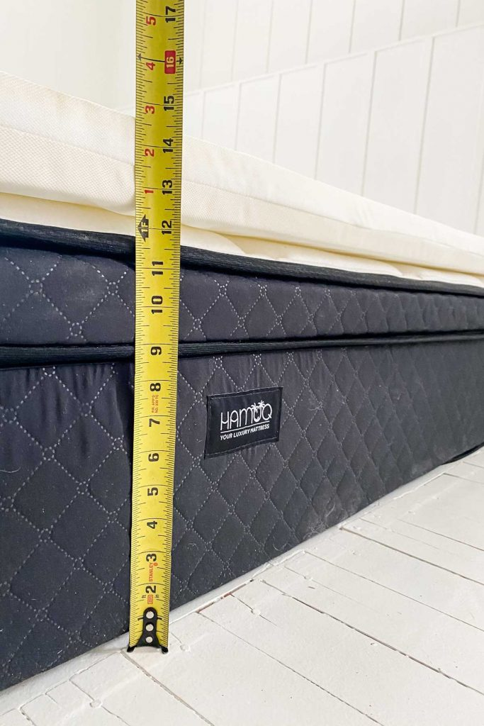 close up of Hamuq mattress with measuring tape showing height of mattress with topper