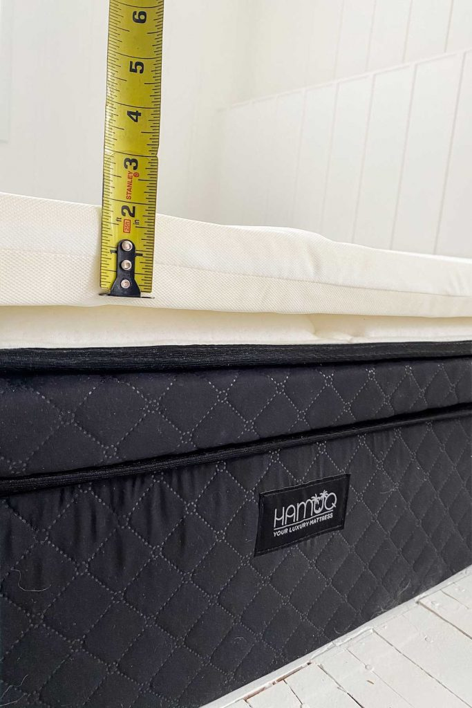 close up of Hamuq mattress with measuring tape showing height of mattress topper