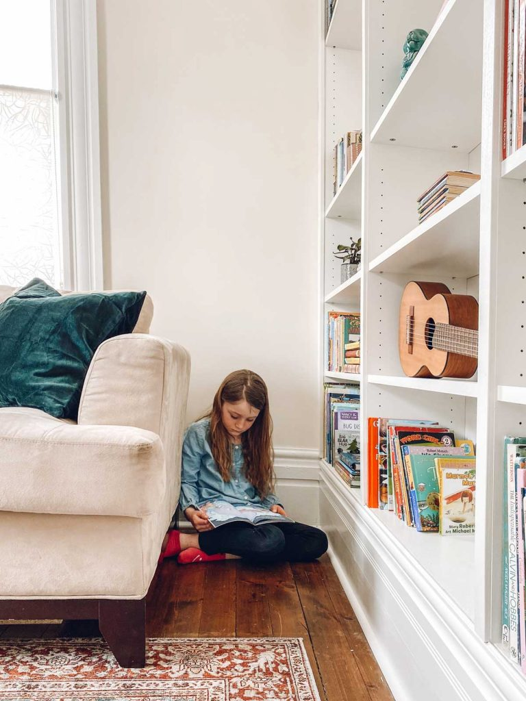 young girl reading a book sitting on the floor in home library between a couch and built in bookshelf