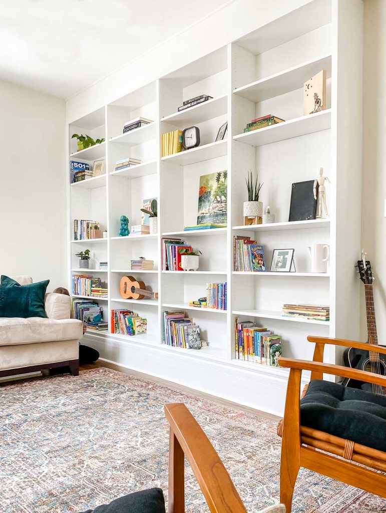 home library floor to ceiling bookcase filled with books, artwork, plants, guitar and picture frames