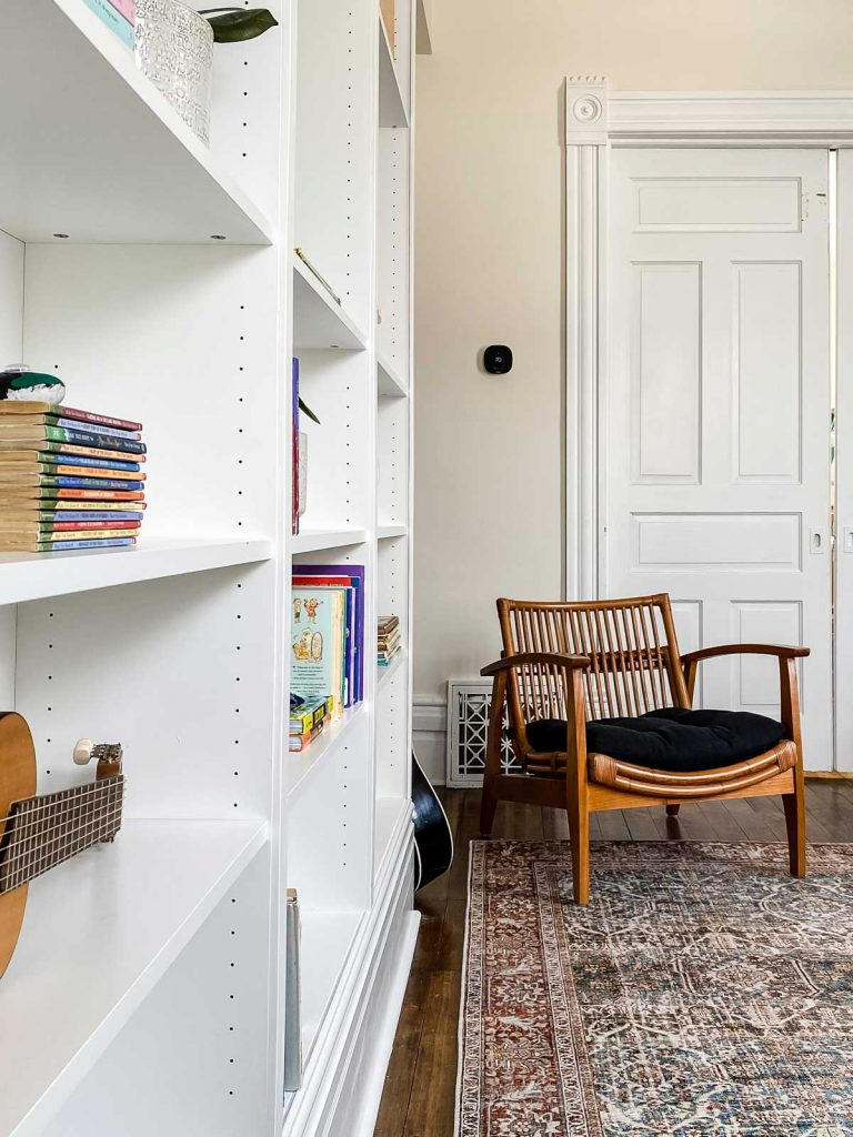 home library with close up of bookshelves on the left looking at wicker accent chair