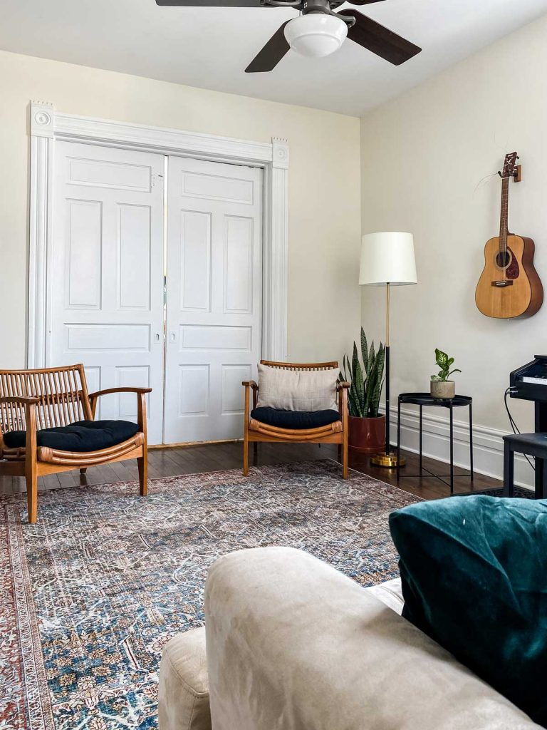 living room with sliding pocket doors accent chairs, plant, lamp and guitar hanging on the wall