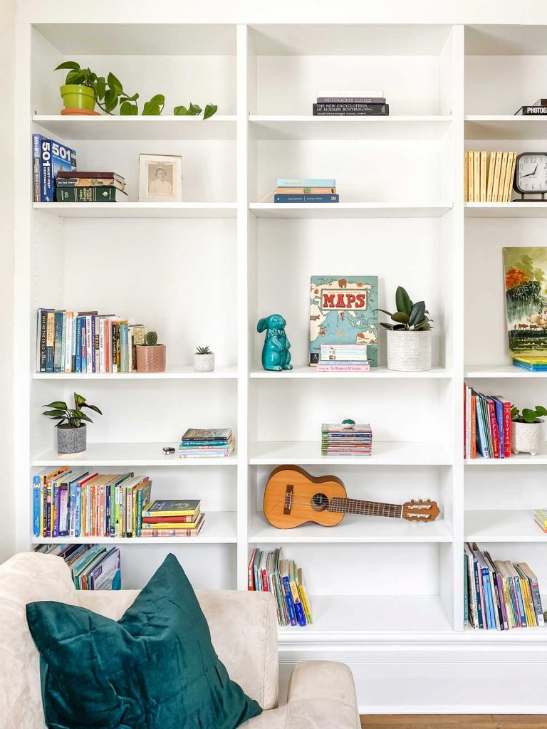 white bookshelf with books, plants, guitar on display in home library