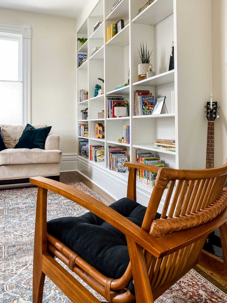 home library built in bookcase filled with books, plants, photos, guitar