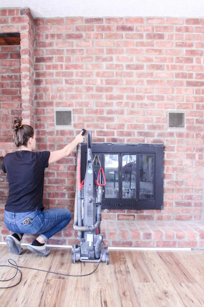 women vacuuming  up any loose debris before painting a brick fireplace