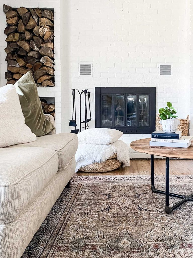 brick fireplace painted white with wood storage to the left and a round coffee table up front