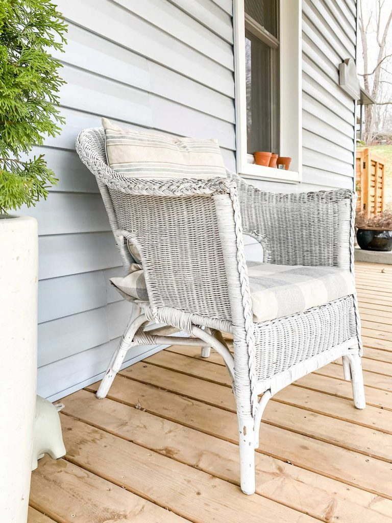 old wicker furniture painted white sitting on front porch